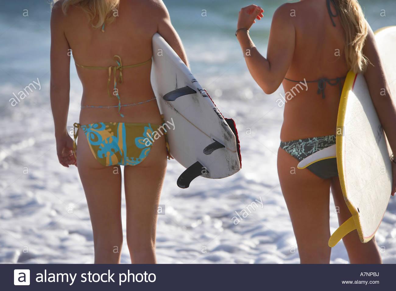 Dos jóvenes mujeres de pie en la playa cerca del mar llevar tablas de surf axilas sección intermedia vista Imagen De Stock