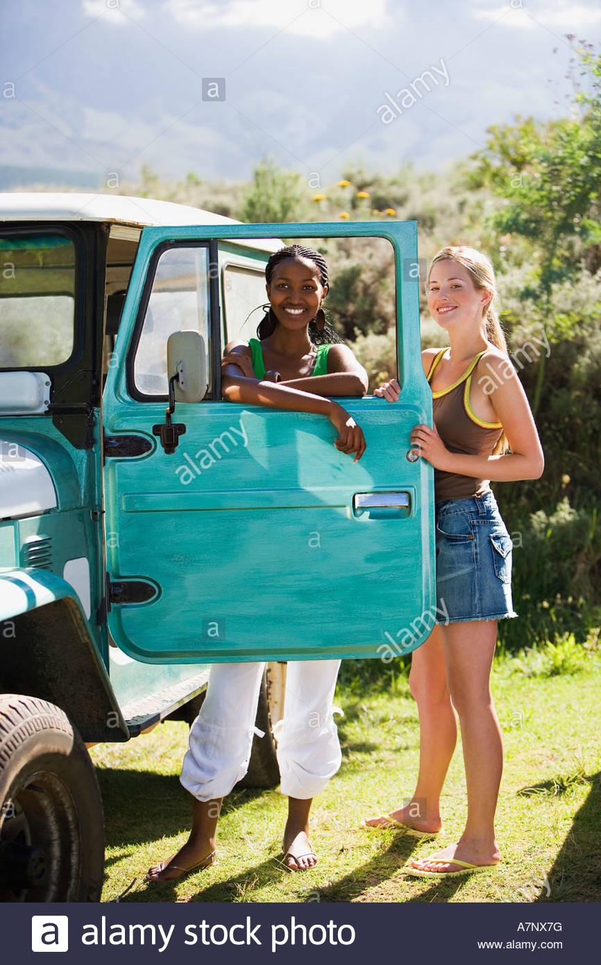 Dos jóvenes mujeres de pie apoyándose en jeep aparcado al lado de la puerta turquesa retrato sonriente Imagen De Stock