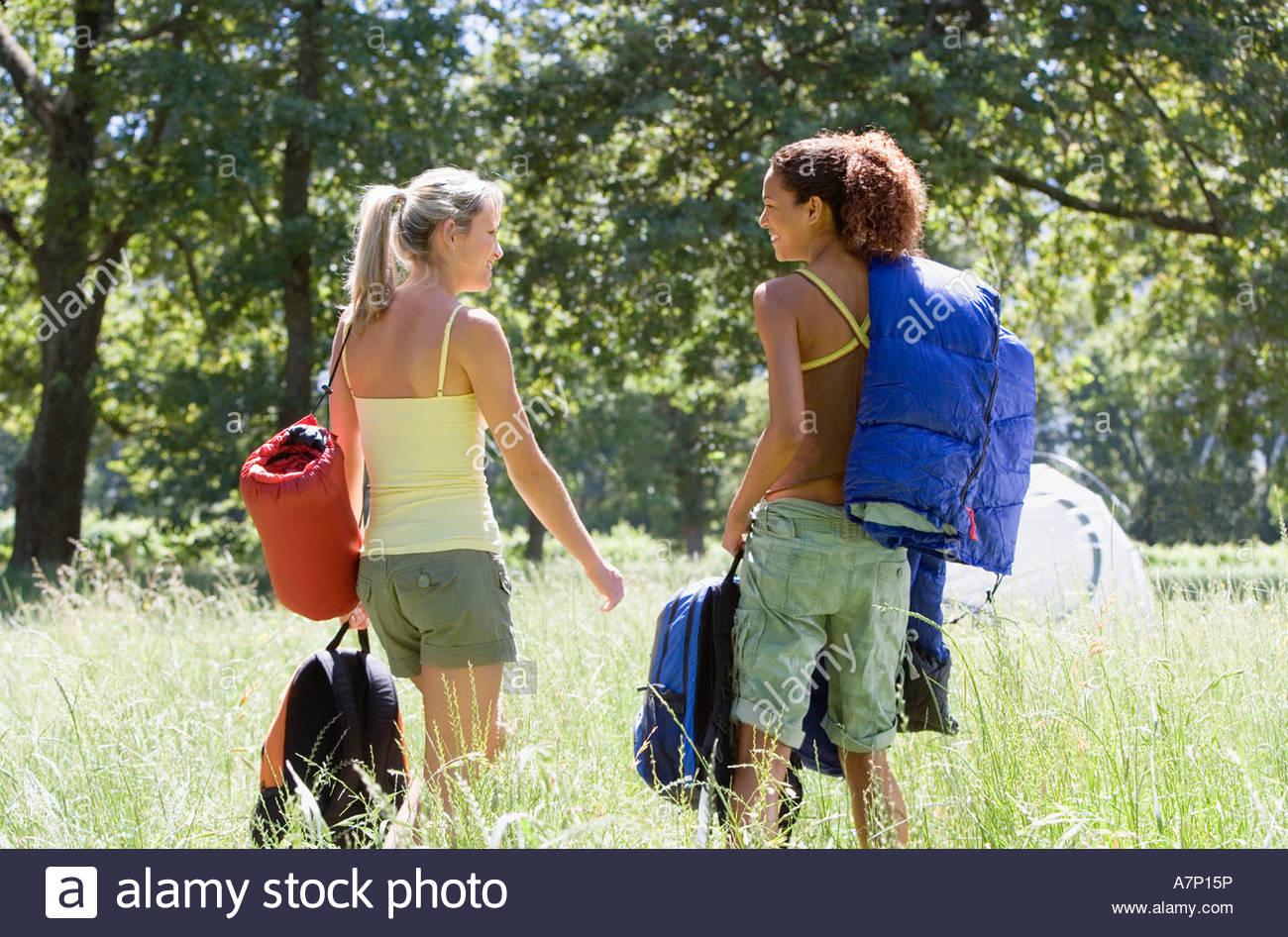 Dos mujeres jóvenes con mochilas y sacos de dormir salir de excursión en Woodland Borrar vista trasera Imagen De Stock