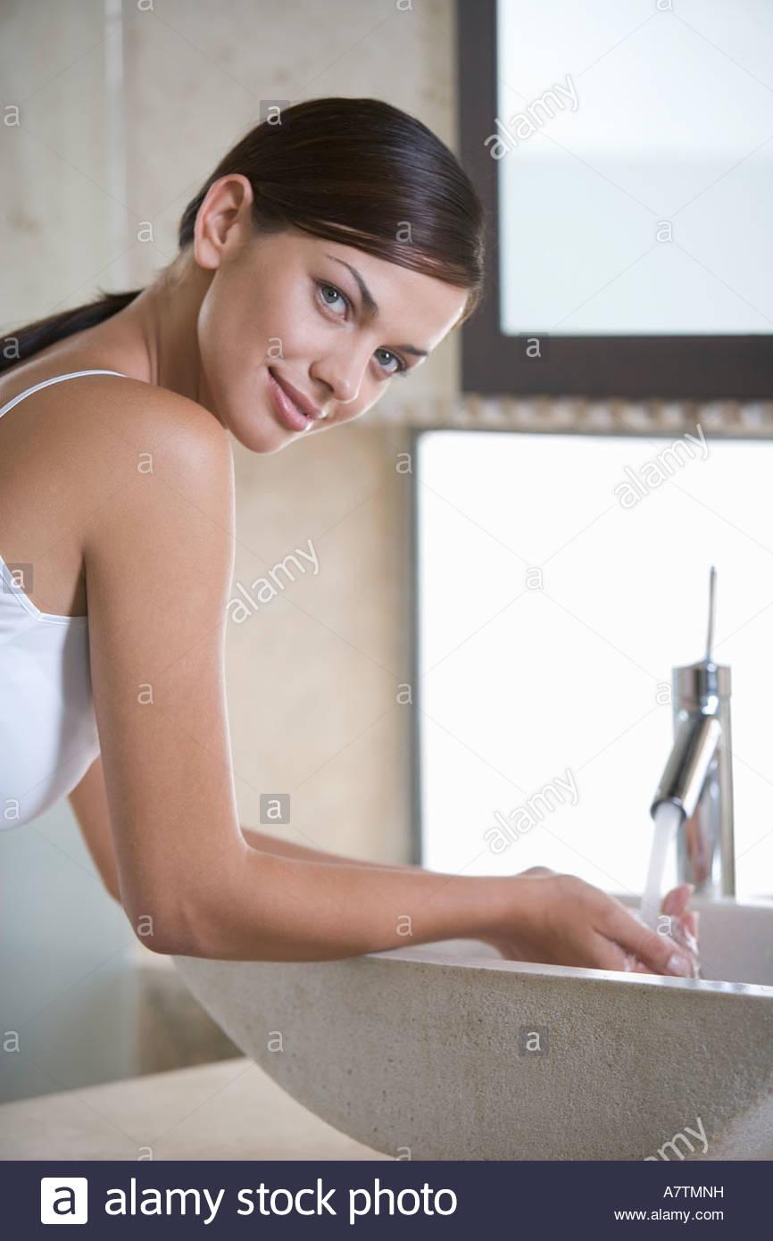 Una mujer lavando en un sumidero Imagen De Stock