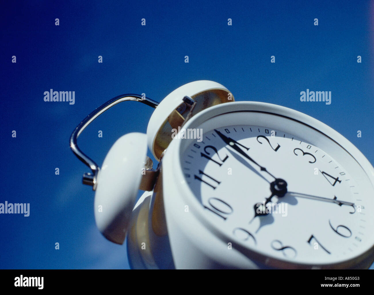 Concepto de imagen blanca, tradicional reloj alarma contra el cielo azul. Imagen De Stock