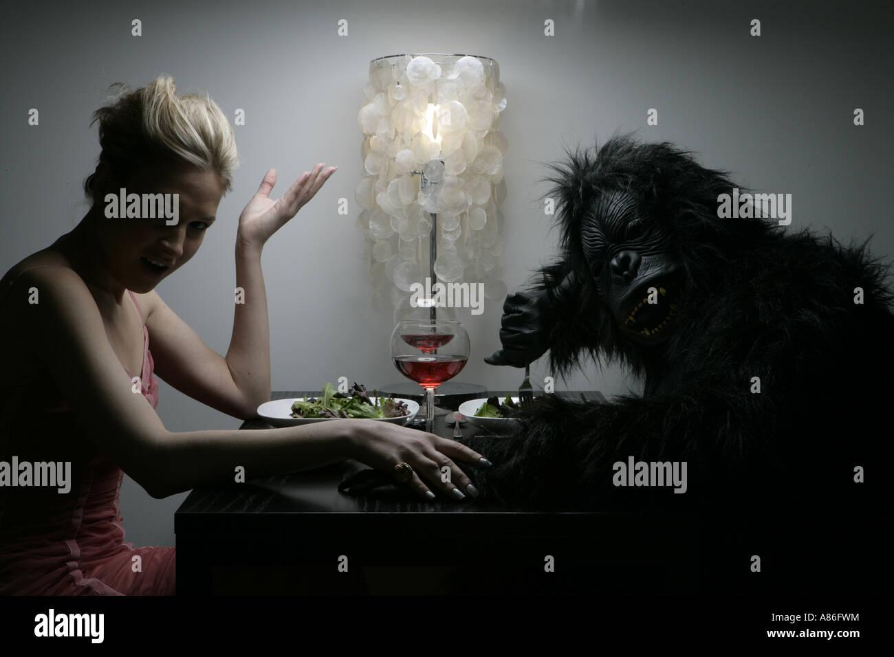 Una mujer es cenar con un hombre en traje de gorila. Foto de stock