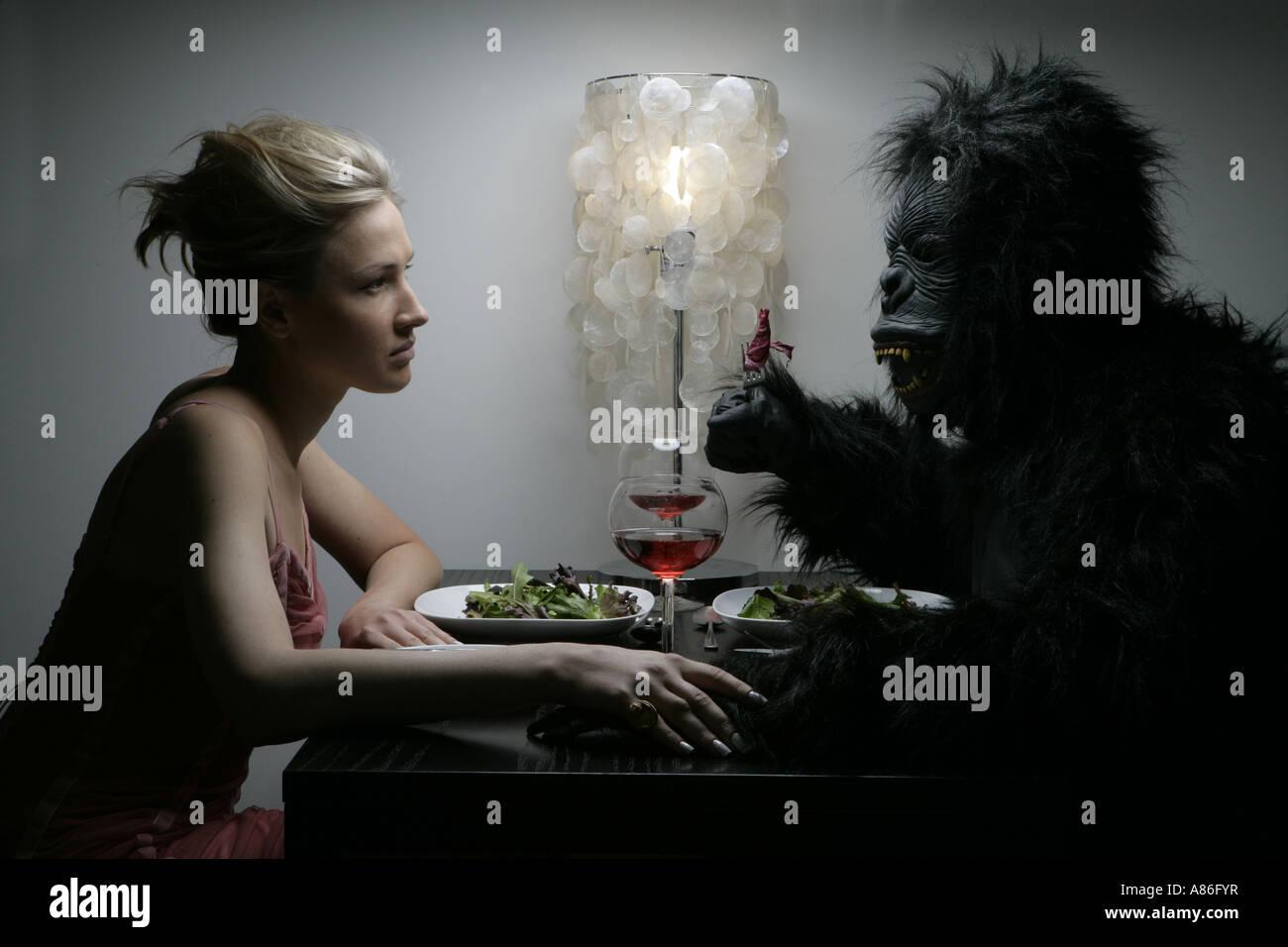 Una mujer es cenar con un hombre en un traje de gorila. Foto de stock