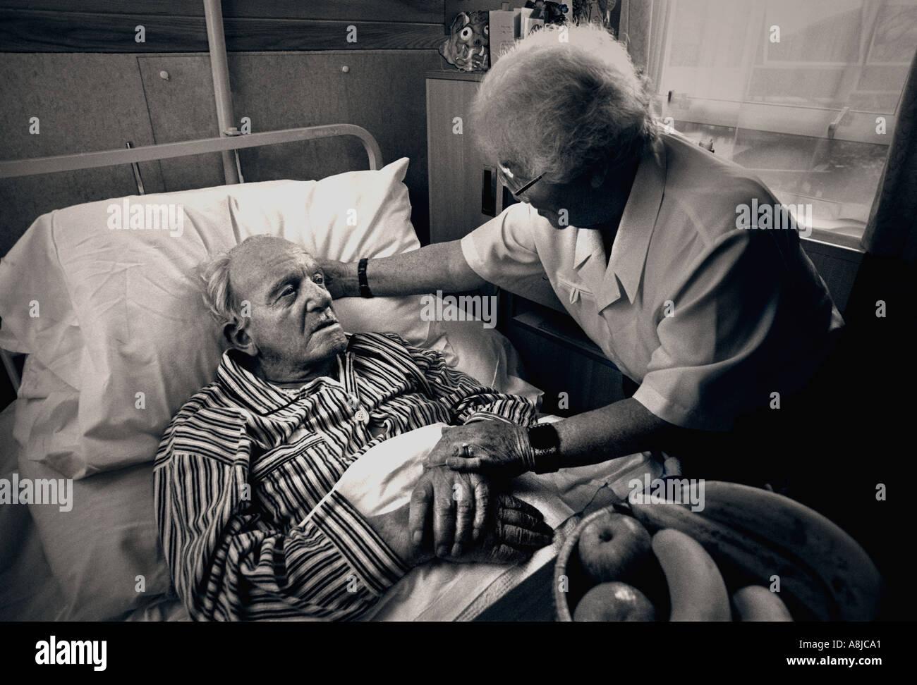 Visitar cuidador Esposa acompañante comodidades anciano caballero en su hogar del cuidado de cama en tonos blanco y negro tratamiento Imagen De Stock