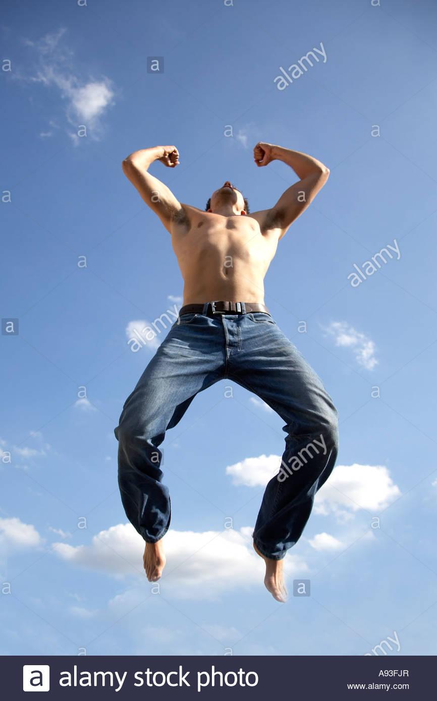 Joven saltando de júbilo contra el cielo azul Foto de stock