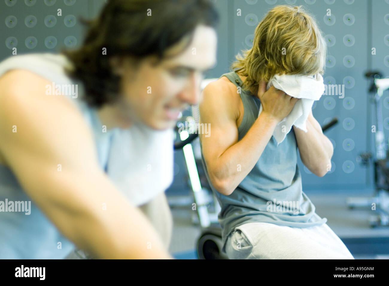 Dos hombres que viajaban en bicicletas de ejercicio, una cara de barrido Imagen De Stock