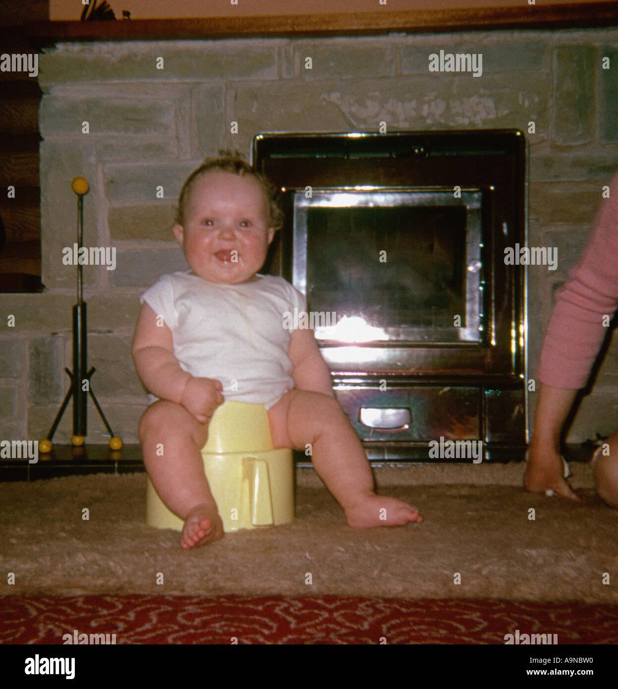 Bebé esté sentado en el asientico con bacinica en frente de fuego 1960 Imagen De Stock