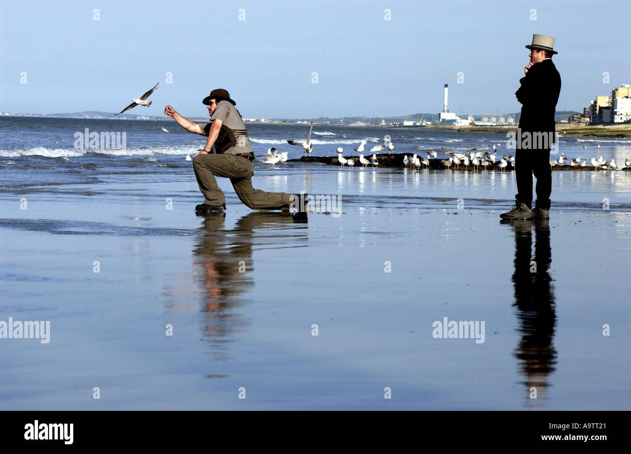 Stone rozando la competencia en la playa de Brighton. Un aspirante lob una piedra, observados por un juez. Foto de stock