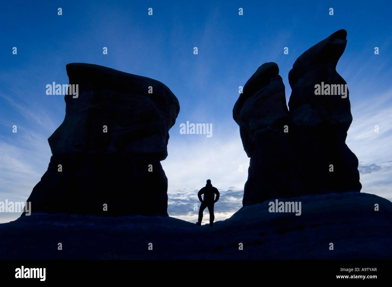 Hombre de pie entre dos características de arenisca en jardín DevilÕs UtahMan interponiéndose entre dos características de arenisca en Devil's Garden Foto de stock