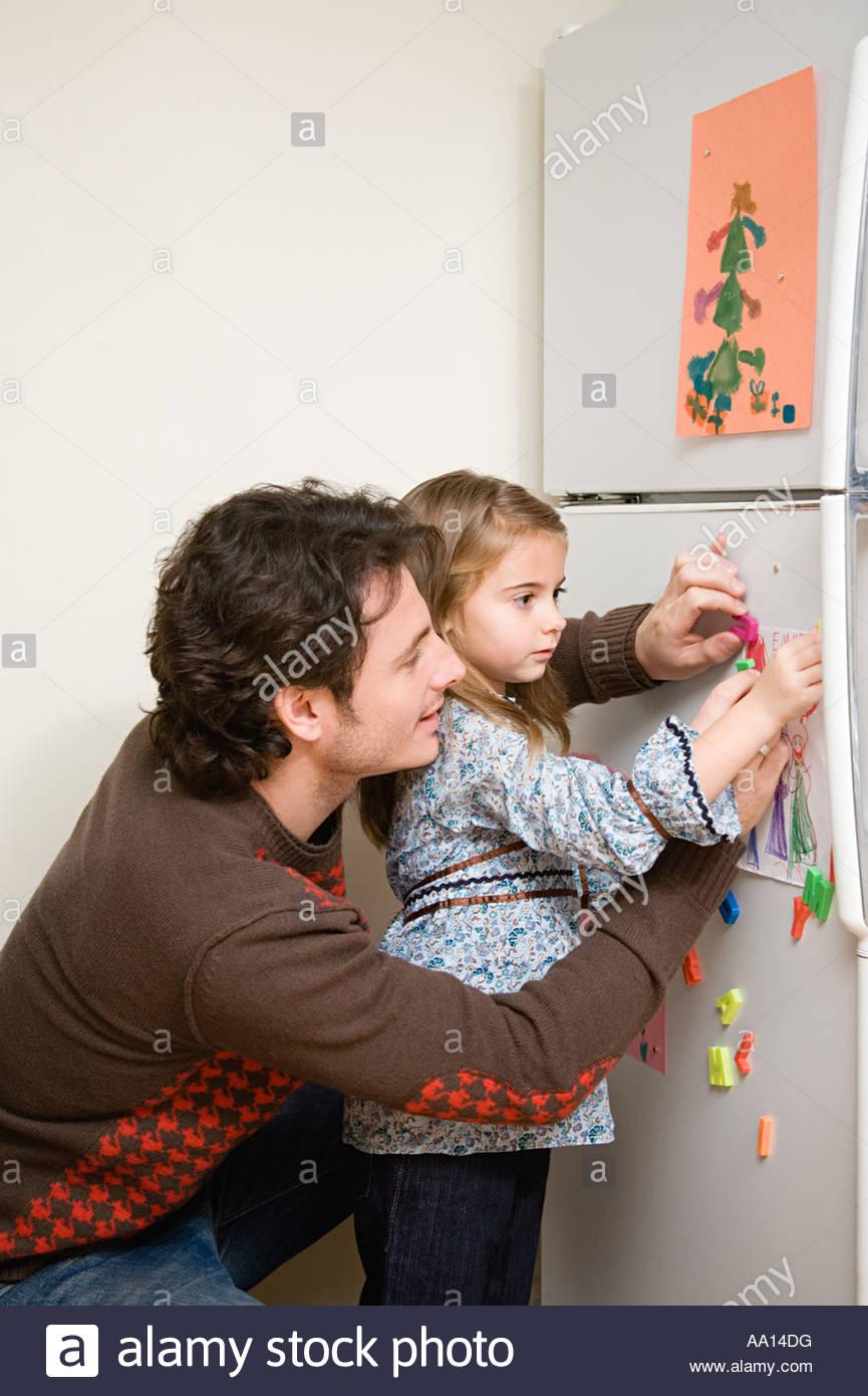 Chica y padre poner imagen en refrigerador Imagen De Stock