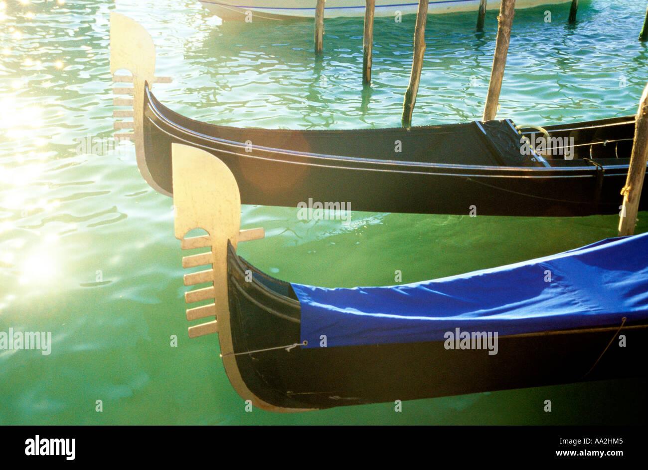 Italia, Venecia, góndolas de Sun sobre la superficie del agua Canale Grande Grand Canal, tallada prows de góndolas amarradas por canal Foto de stock