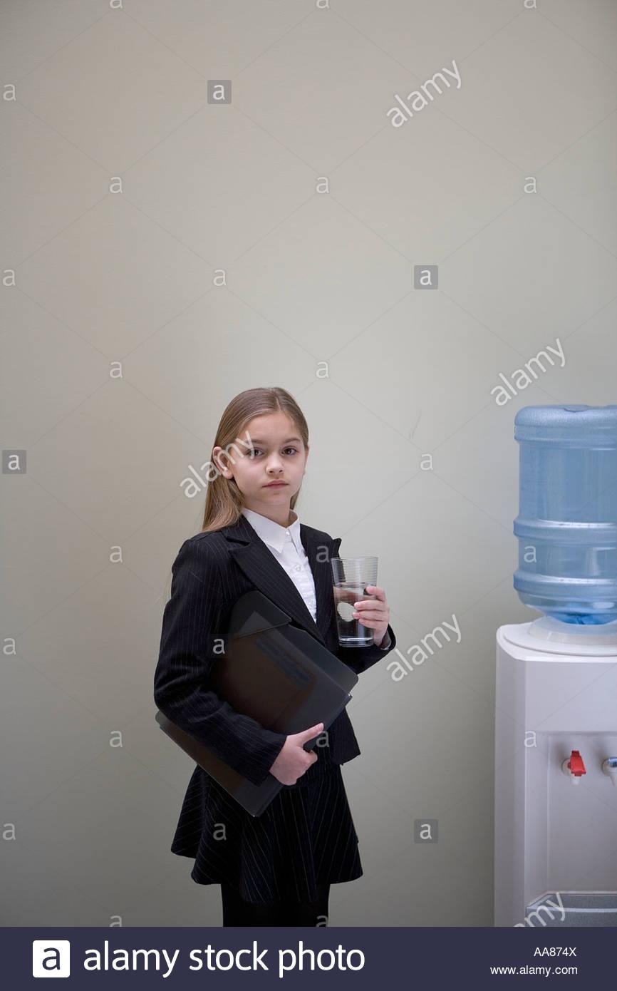 Niña en traje de negocios por el enfriador de agua Imagen De Stock