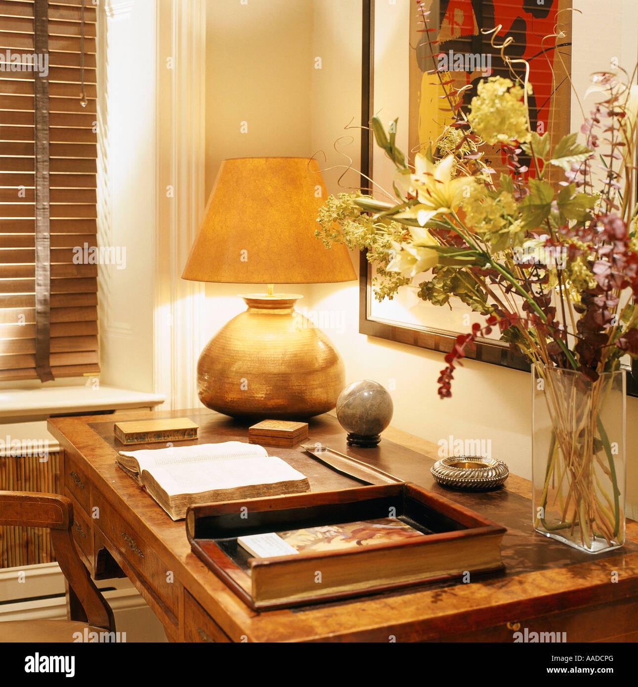 Oro lámpara encendida y el arreglo floral en el escritorio con libro abierto Imagen De Stock