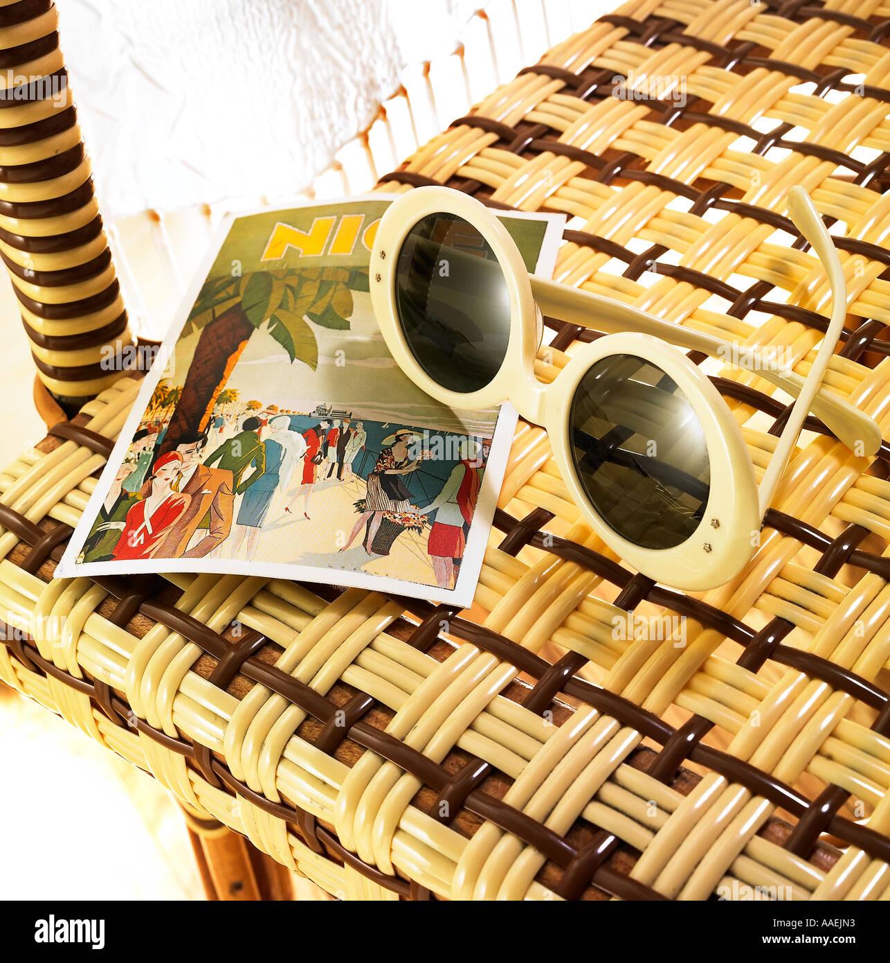 Gafas de sol y postal en silla bistro Imagen De Stock