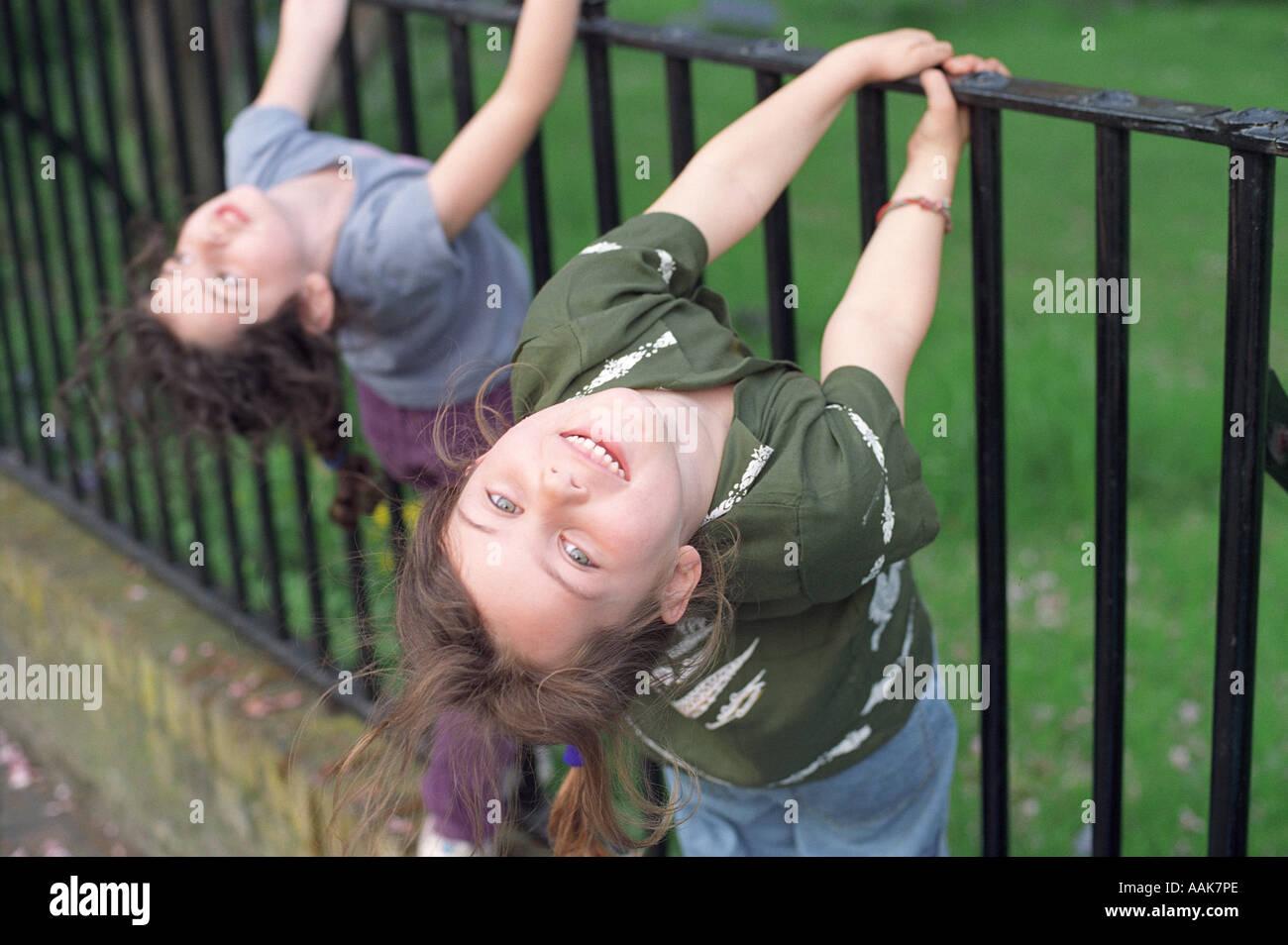 Dos niñas de seis años jugando en rejas metálicas, Londres, Reino Unido. Foto de stock