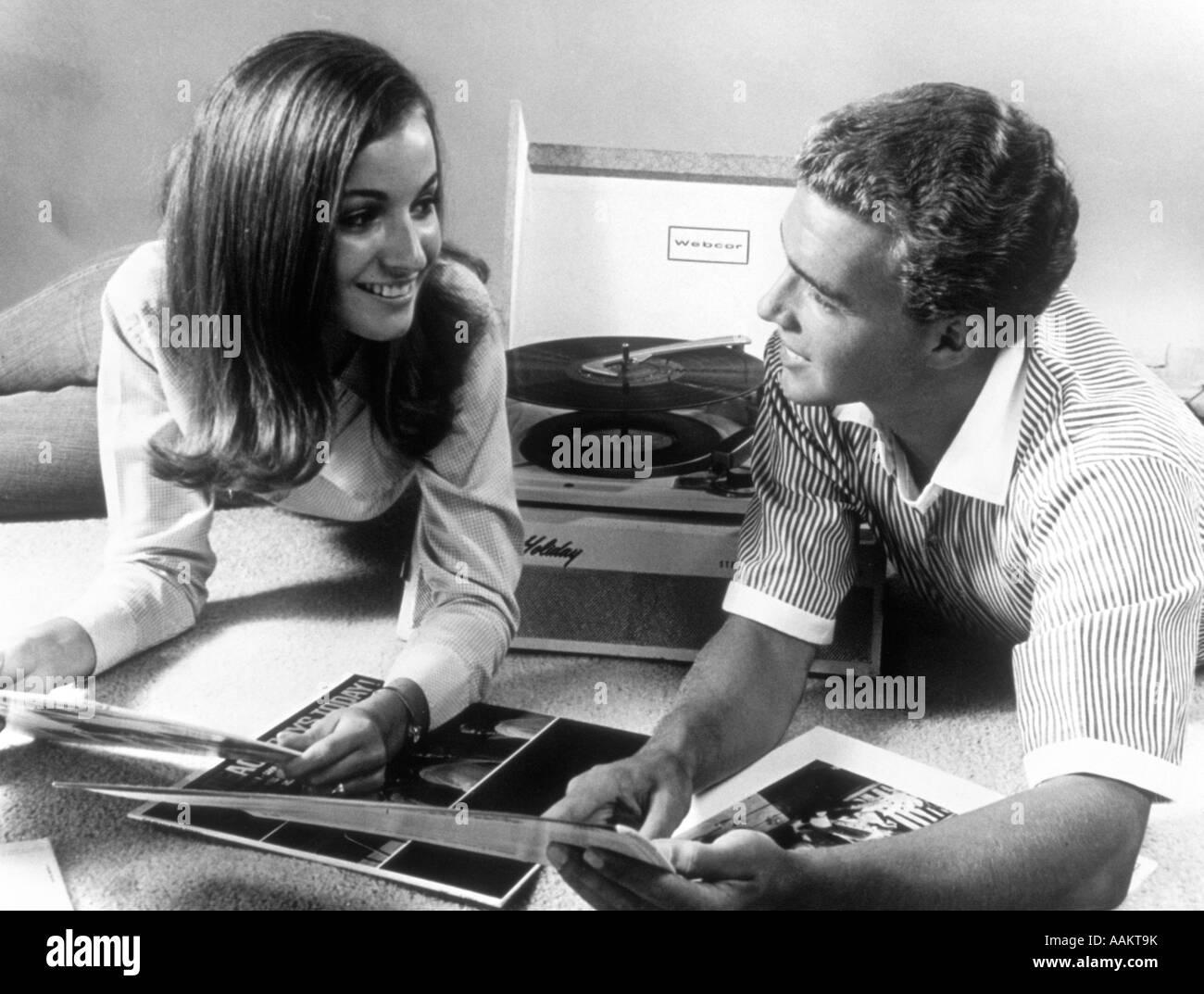 1960 pareja de adolescentes jugando LP de vinilo en el fonógrafo portátil Imagen De Stock