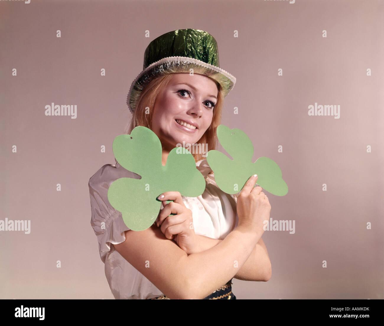 1960 1970 RETRO mujer irlandesa sonriente sosteniendo GREEN SHAMROCKS y llevar gorro de FIESTA VERDE Imagen De Stock