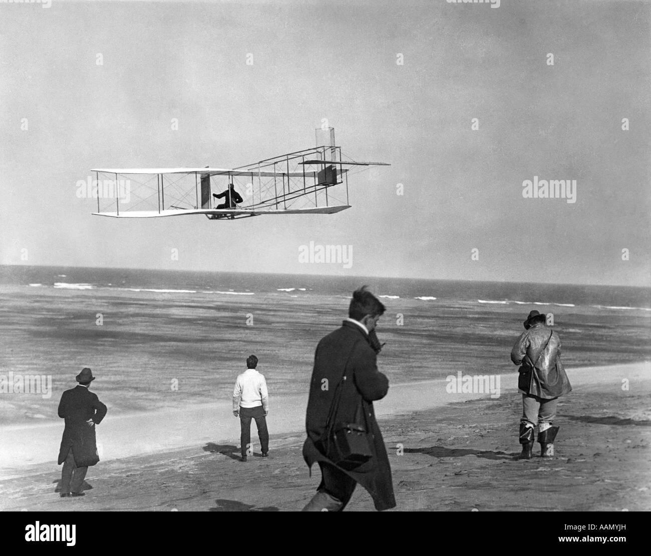 Uno de los hermanos Wright planeador volando por el océano y espectadores en la playa debajo de Kitty Hawk, Imagen De Stock