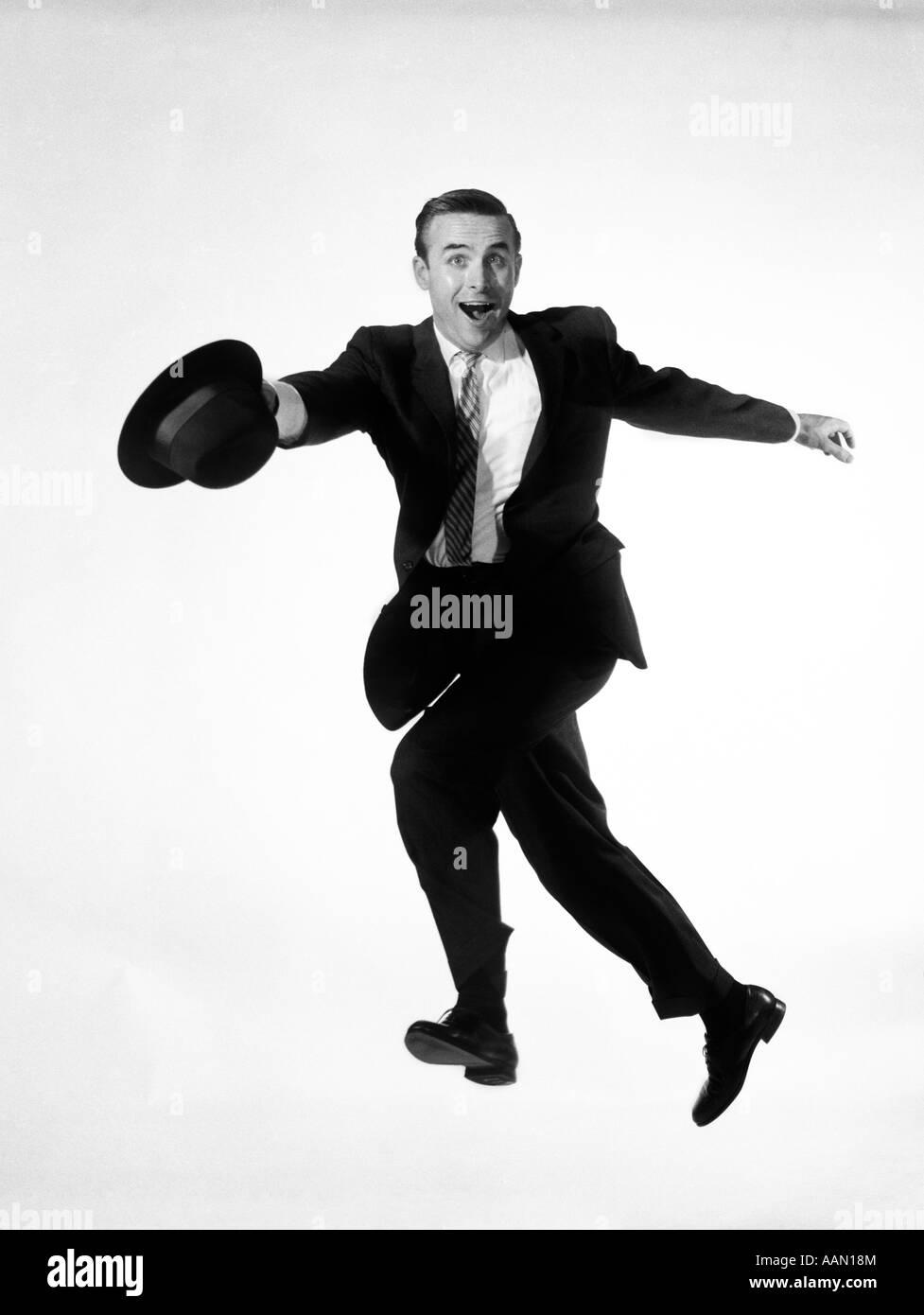 1960 hombre en traje de negocios saltar en el aire mientras se ejecuta el sombrero en la mano GOOFY DIVERTIDA EXPRESIÓN EN SU ROSTRO PRISA VENDEDOR CHIFLADO Foto de stock