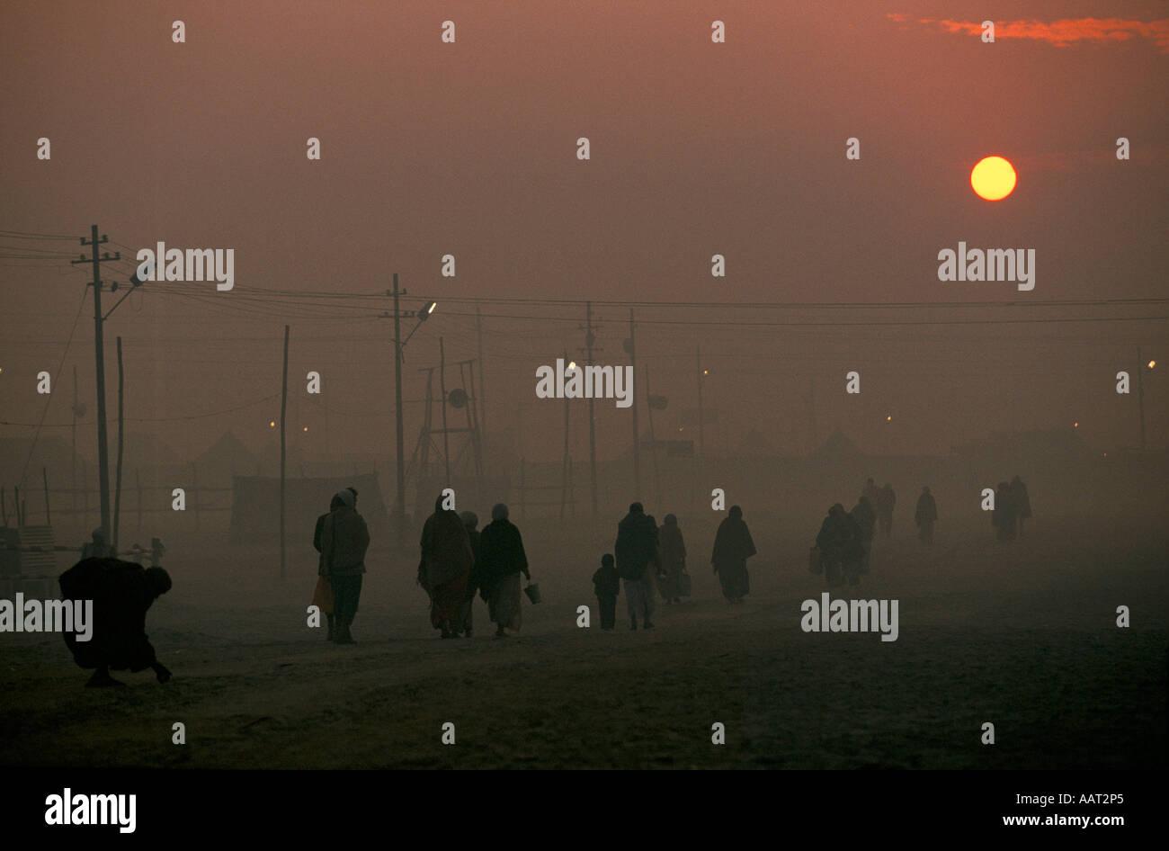 KUMBH MELA INDIA 2001 como el sol se pone el humo de los fuegos de leña hace una espesa niebla peregrinos regresen Foto de stock