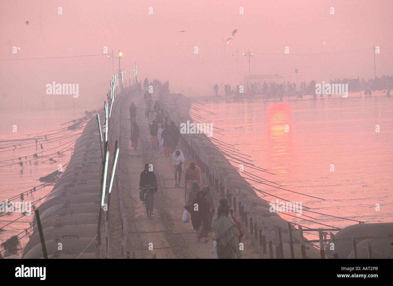 KUMBH MELA INDIA 2001 COMO EL SOL peregrinos hacen su camino de regreso a través de los puentes provisionales a Foto de stock
