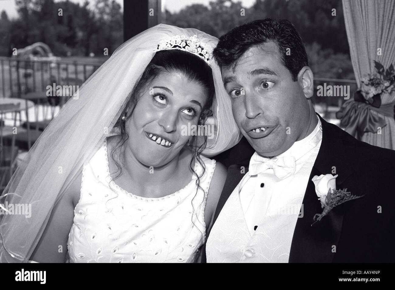 Goofy pareja en boda haciendo muecas para el novio y la novia tonta feliz blanco y negro horizontal Foto de stock