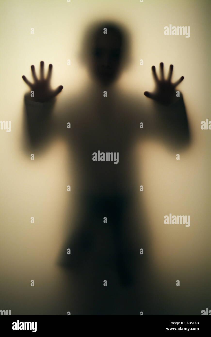 Chico 7, 8, 9, 10, 11, 12, 13, 14 años de edad figura detrás de pared transparente Imagen De Stock