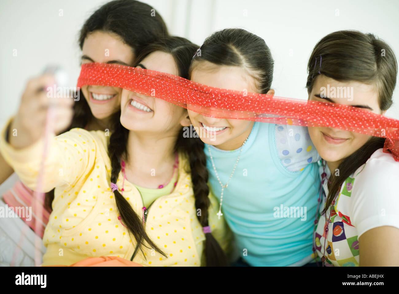 Cuatro amigas jóvenes sosteniendo la bufanda delante de los ojos, uno toma de fotografía con teléfono Imagen De Stock