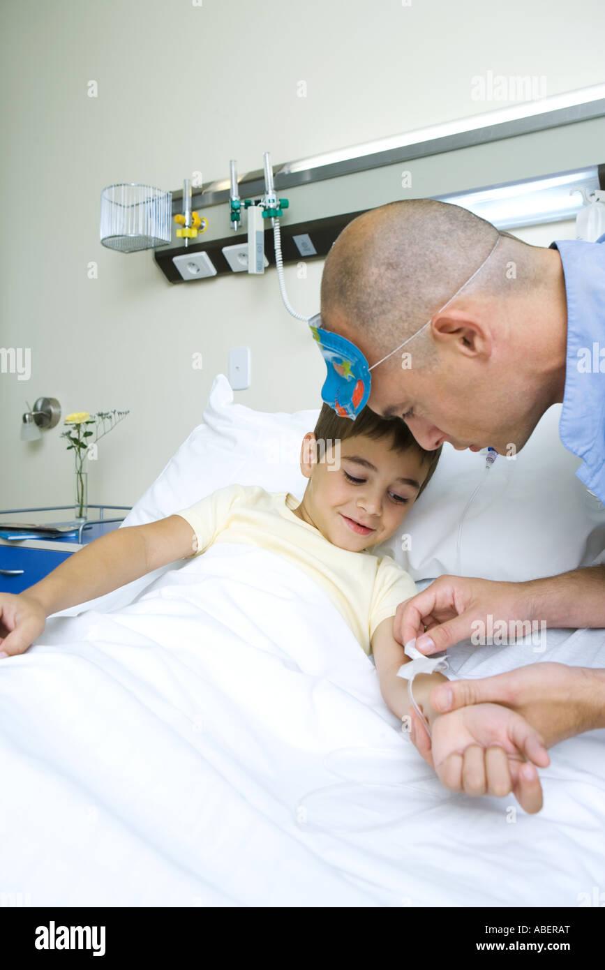 Niño acostado en la cama del hospital, la enfermera IV de ajuste Foto de stock