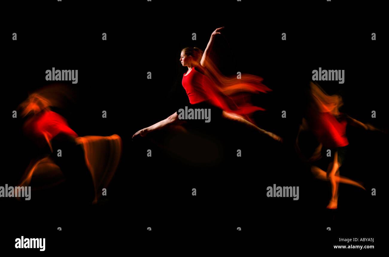 La bailarina vestidos de rojo triple salto la captura de movimiento Imagen De Stock
