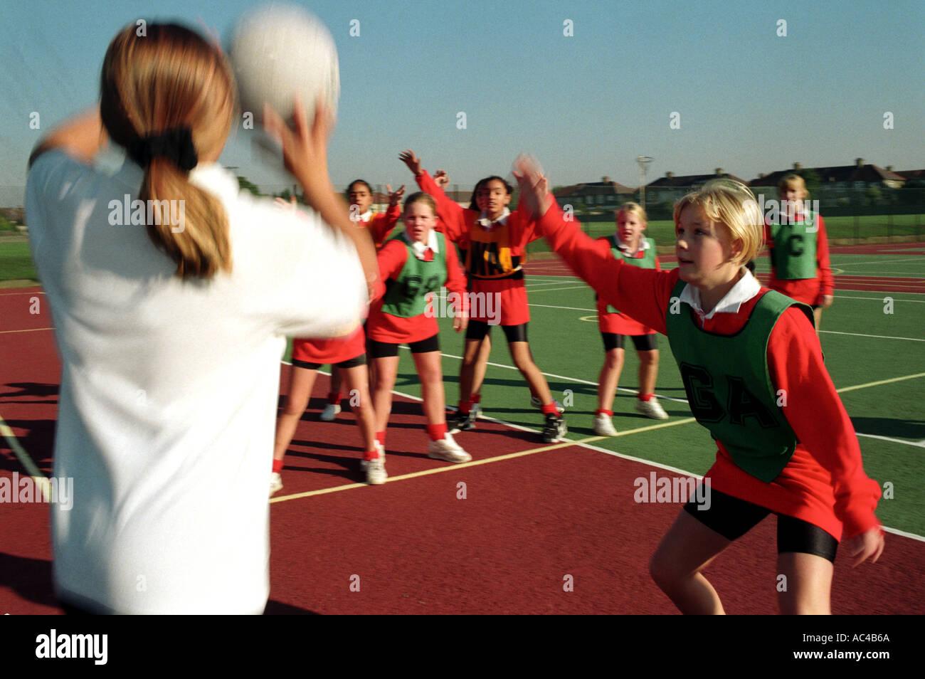 Las mujeres jugando baloncesto / baloncesto en una escuela secundaria Imagen De Stock