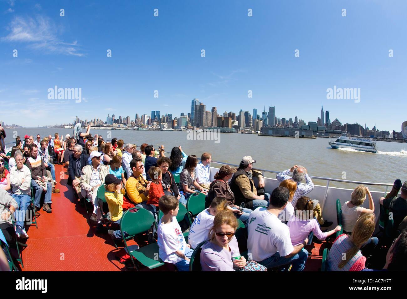Los turistas admirar vistas de Manhattan en sol de primavera de Circle Line ferry viaje alrededor de Nueva York Imagen De Stock