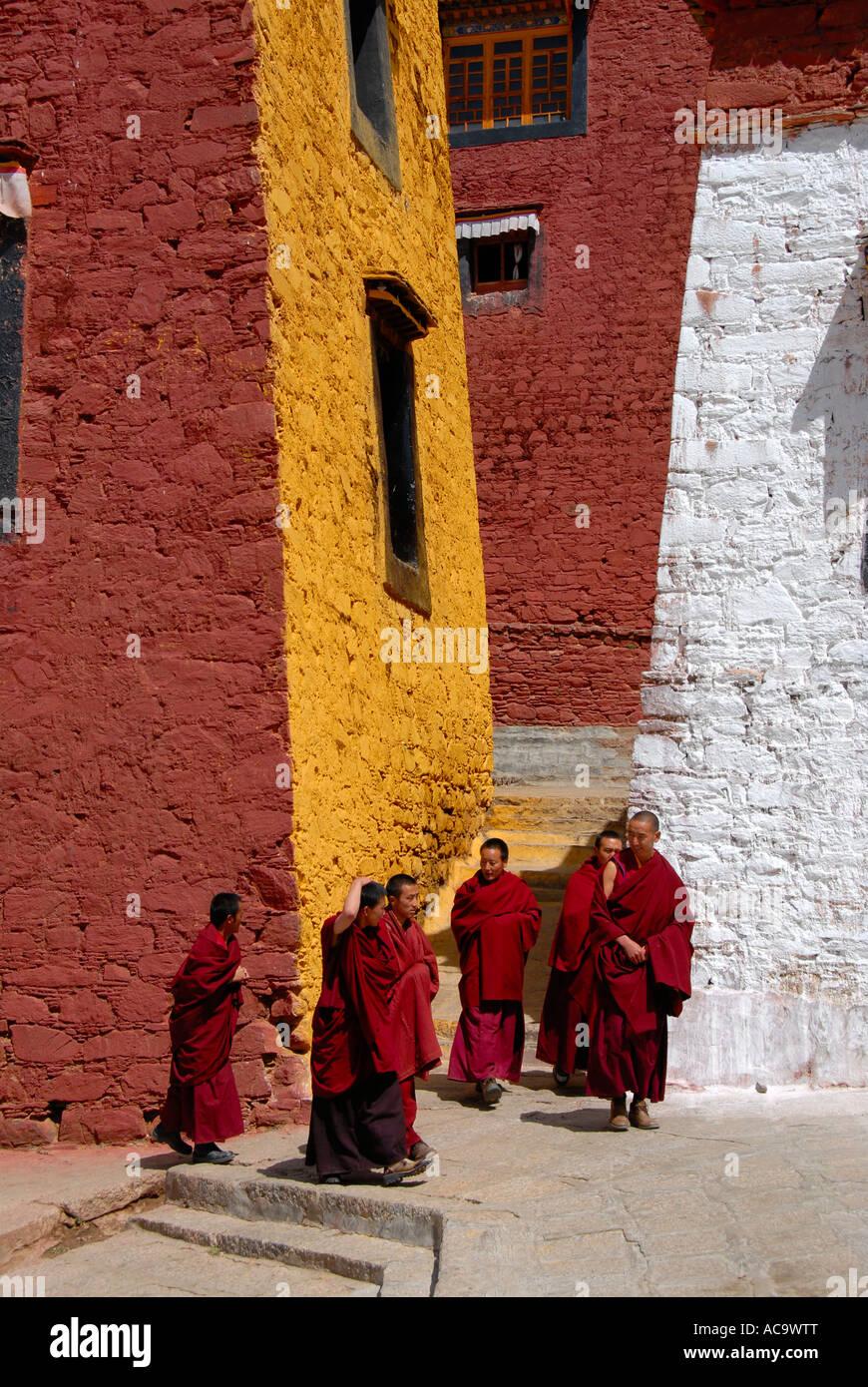 Los monjes tibetanos caminando por el ocre rojo y paredes pintadas de blanco el Monasterio Ganden Tibetano China Foto de stock