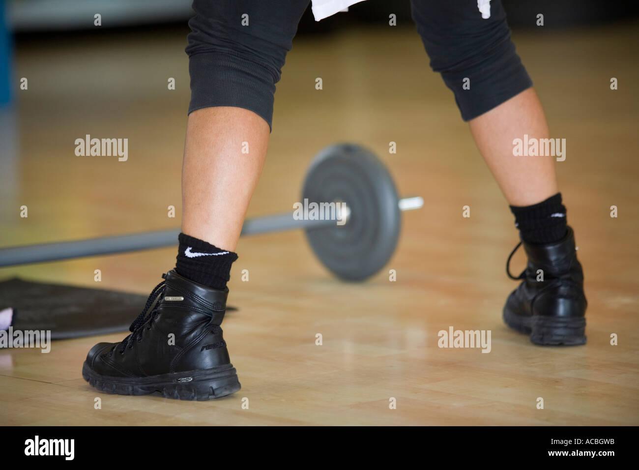 Ejercítese en el gimnasio: detalle de las piernas y el peso pesado Imagen De Stock
