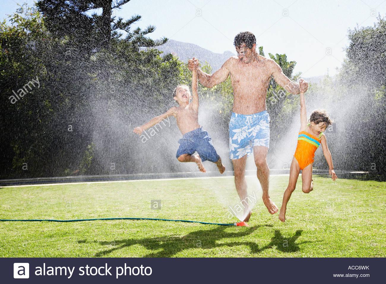Un padre jugando con sus hijos en un rociador Foto de stock