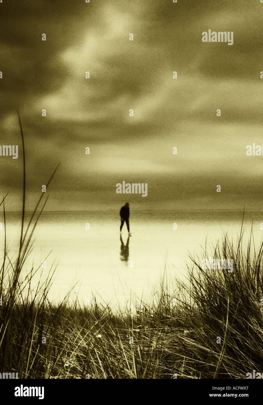 Foto de un hombre que camina a lo largo de una playa de arena solo Imagen De Stock