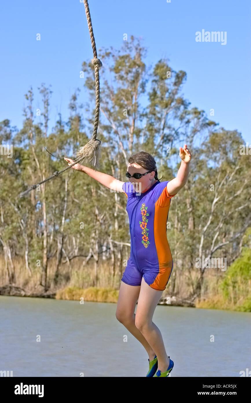 Una adolescente vistiendo googles acaba de dejar pasar una cuerda y cae en el río Foto de stock