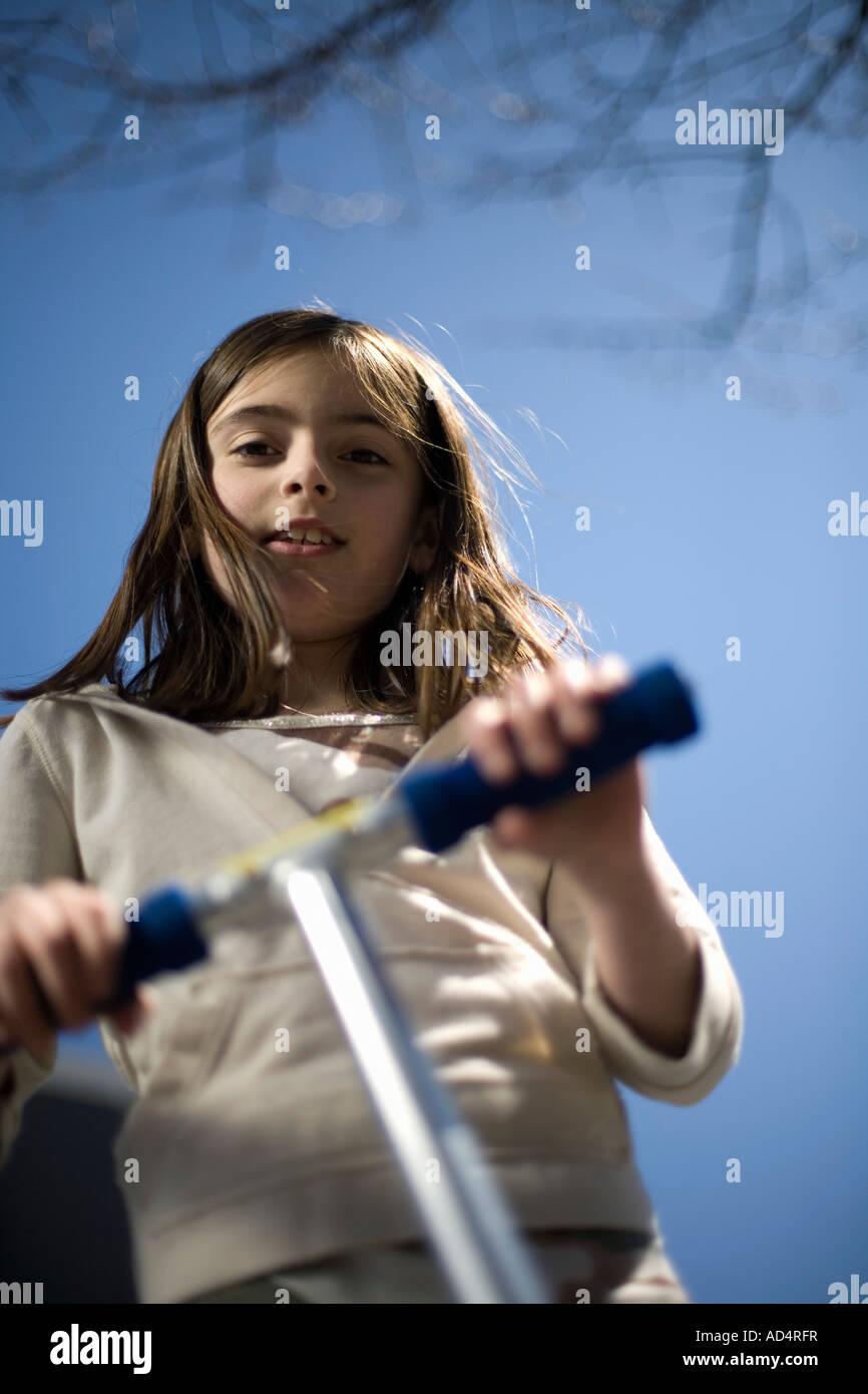 Ángulo de visión baja de una chica con un scooter de empuje Imagen De Stock