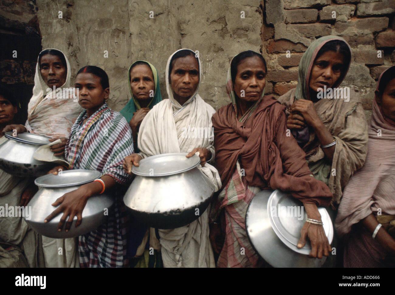 Las personas pobres con ollas colas para obtener alimentos para sus familias en la misión de la Madre Teresa en Calcuta, India Foto de stock