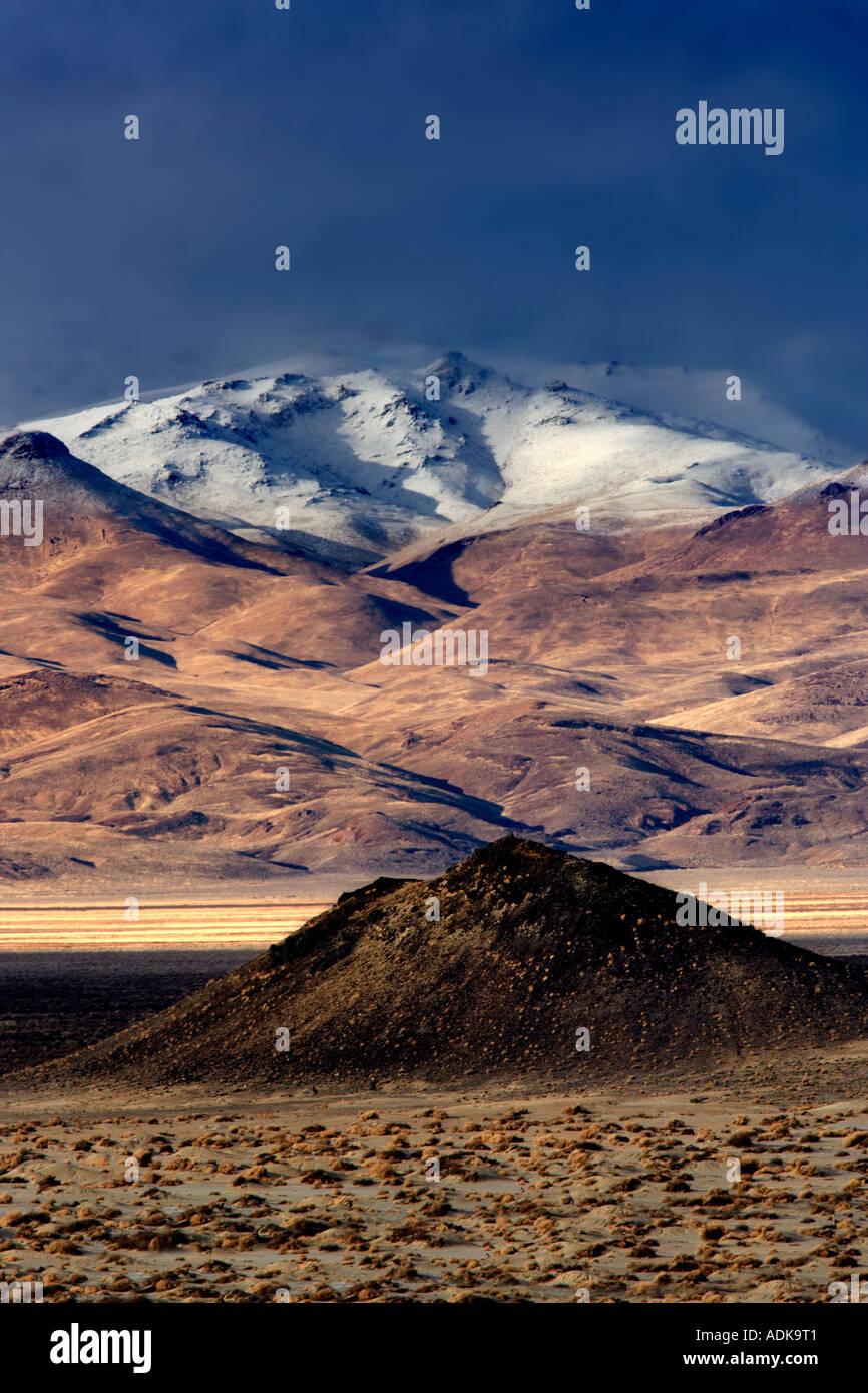 Pequeño cono de ceniza y montañas cubiertas de nieve Desierto Black Rock de Nevada Área Nacional de Conservación Foto de stock