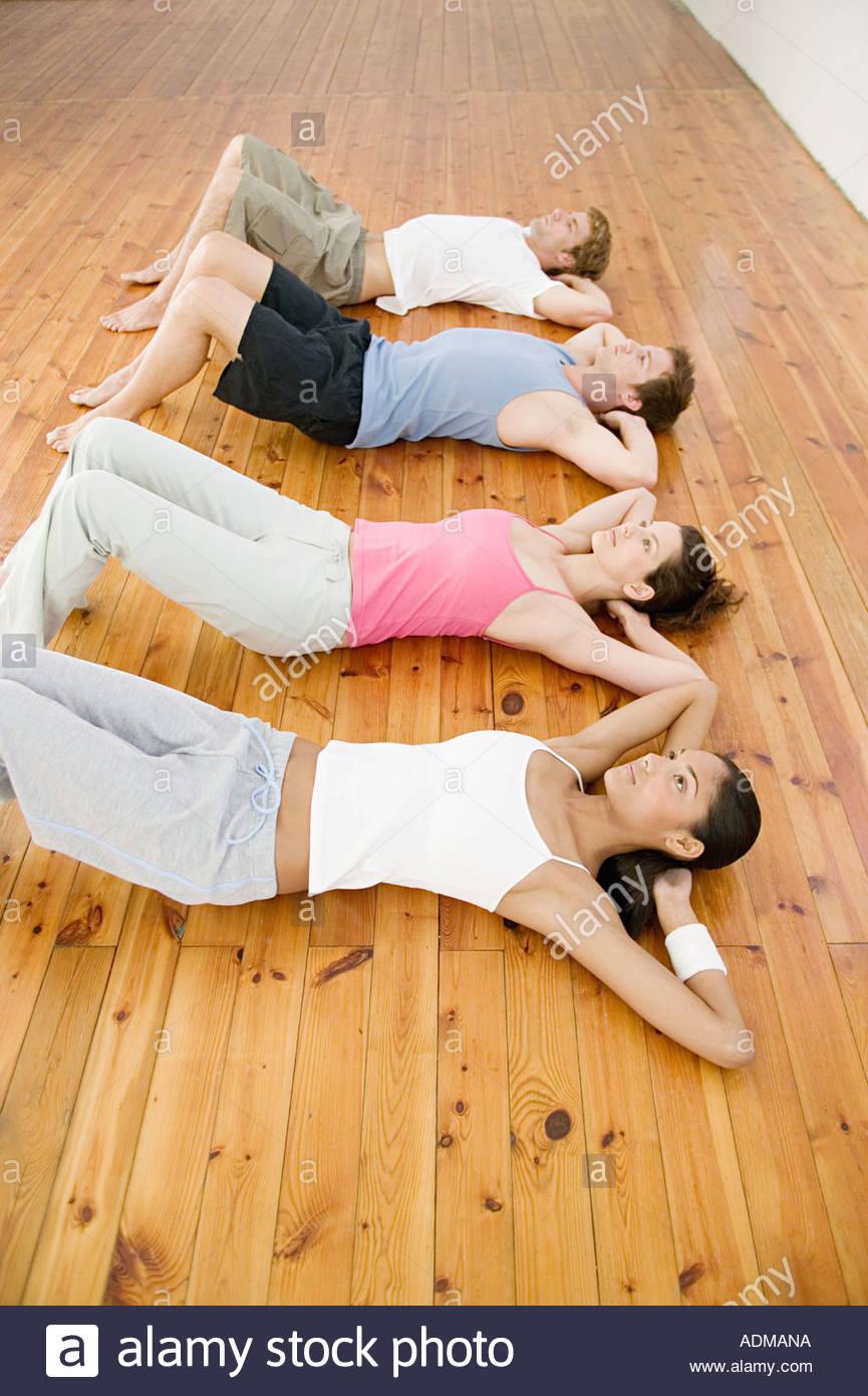 Los hombres y mujeres que realizan el sentarse ups Imagen De Stock