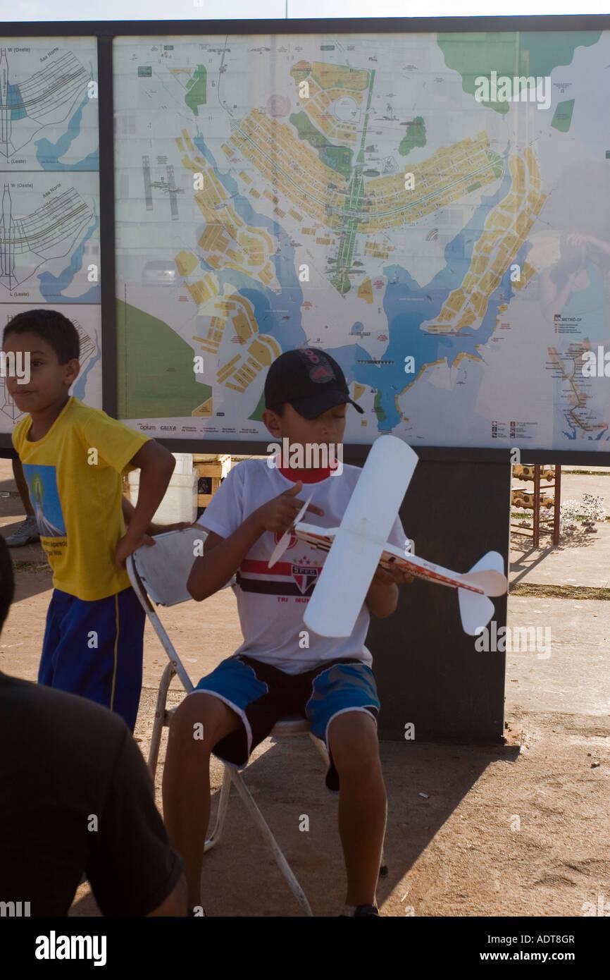 Niño jugando con el avión de juguete delante del mapa de Brasilia Foto de stock