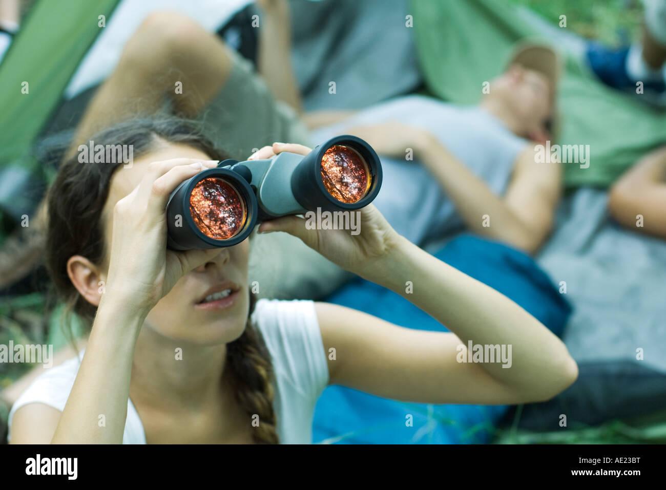 Mujer mirando a través de binoculares, senderismo compañeros descansando en segundo plano. Imagen De Stock