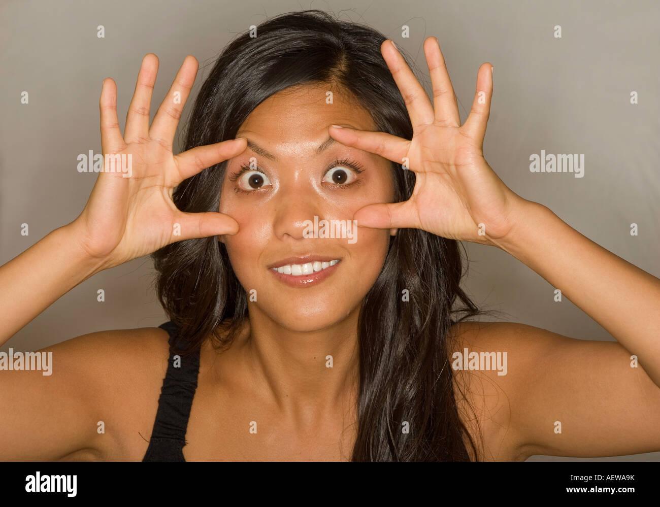 Hermosa joven mujer asiática abultamiento de los ojos con los dedos extendidos Foto de stock
