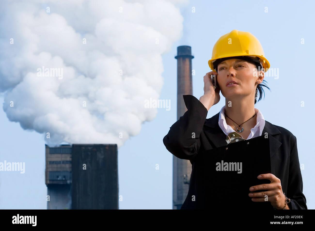 Una hermosa mujer de pelo oscuro en su teléfono móvil de pie delante de una fábrica de bombear hacia afuera la contaminación de sus chimeneas Foto de stock