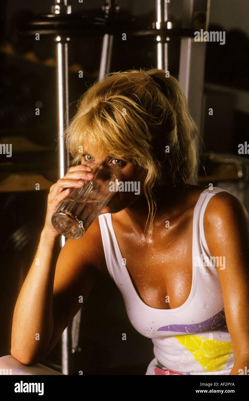 Una joven mujer bebe un vaso de agua después de un arduo entrenamiento Imagen De Stock