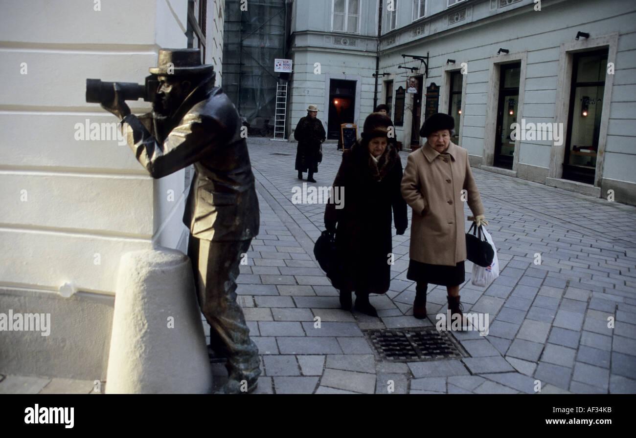 Gracioso escultura de bronce de un fotógrafo equipado con teleobjetivo en la calle Laurinska, Bratislava, Eslovaquia. Foto de stock