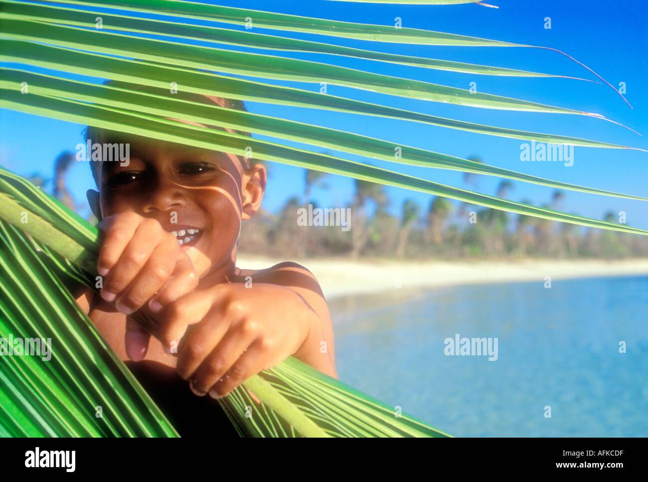 Fiji joven chico mirando a través de las frondas de palma Yasawa Islands Fiji Océano Pacífico Sur Imagen De Stock
