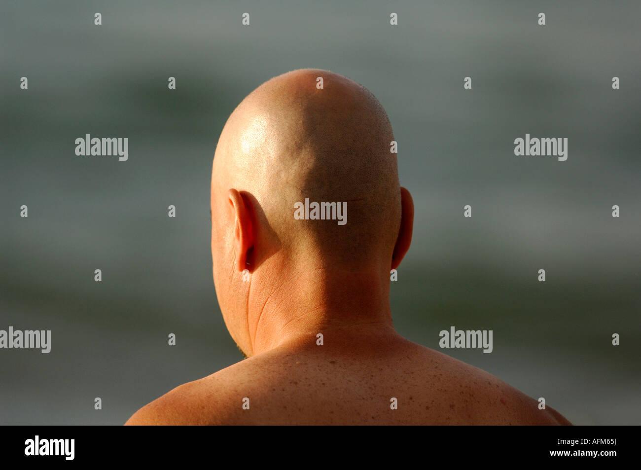 Un encabezado skinheaded calva hombre caballero macho muchacho sin camisa en bare chested de pie en la playa en Foto de stock