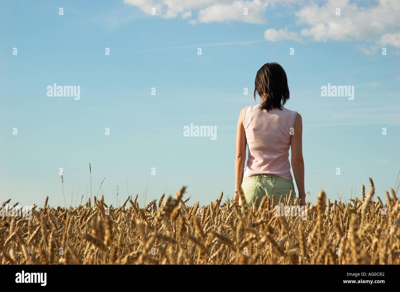 Mujer joven en el campo de trigo mirando a distancia Imagen De Stock